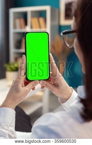 Woman Hands Vertically Holding Cellphone With Green Screen, Homey Atmosphere