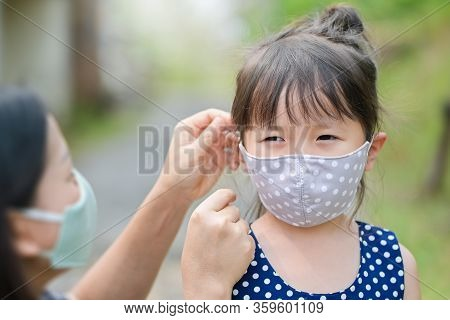 Mother Is Wearing A Cloth Mask For Little Girl Protect Herself From Coronavirus When Child Leave The