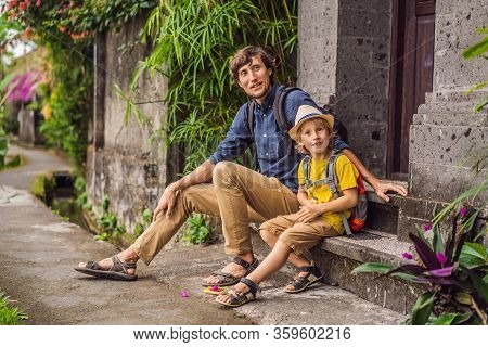 Father And Son Tourists In Bali Walks Along The Narrow Cozy Streets Of Ubud. Bali Is A Popular Touri