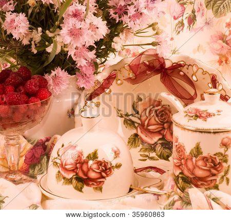 Vintage tea in elegant tableware, raspberry and flowers