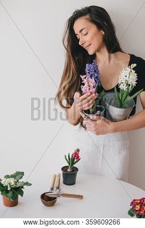 Young Woman Gardener Taking Care For Plants And Home Flowers, Wearing Apron. Home Gardening And Slow