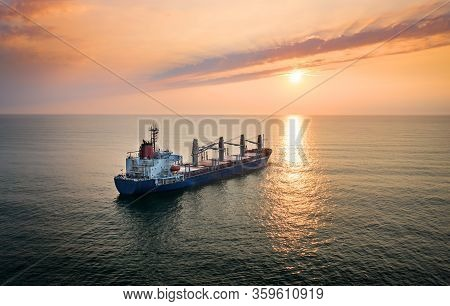 Cargo Ship In The Ocean On The Sunrise.