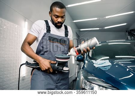 African Man, Auto Service Worker, Wearing White T-shirt And Gray Overalls, Puts Special Wax Or Polis