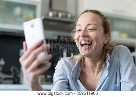Young Smiling Cheerful Pleased Woman Indoors At Home Kitchen Using Social Media Apps On Mobile Phone