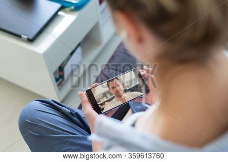 Woman At Home Relaxing On Sofa Couch Using Social Media On Phone For Video Chatting With Her Loved O