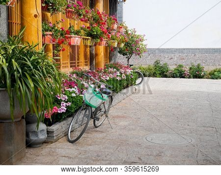 Bicycle Parking In Front Of The House With Little Garden Full Of Colorful Flowers