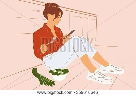 Young Woman Sitting With Phone On The Kitchen Floor, Eating Salad While Relaxing At Home. Healthy Ea