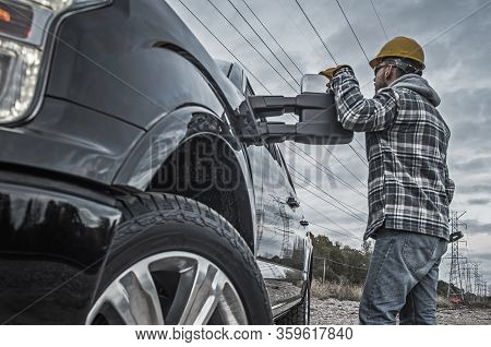 Industrial Worker And Truck. Caucasian Electric Power Worker In His 30s And His Field Job. Staying N