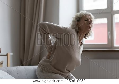 Elderly Middle Aged Woman Suffering From Sudden Sharp Back Pain.