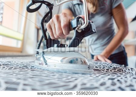 Seamstress with tailor iron ironing fabric