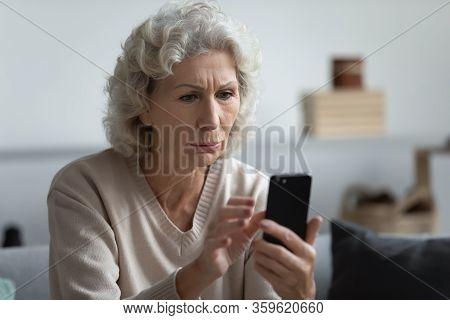 Senior Mature Retired Woman Reading Unpleasant News In Social Media.