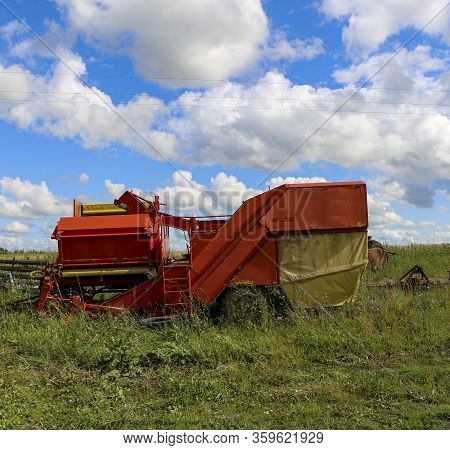 Silage And Forage Harvesting Equipment Is Standing On The Edge Of The Field, Waiting For Work. A Har
