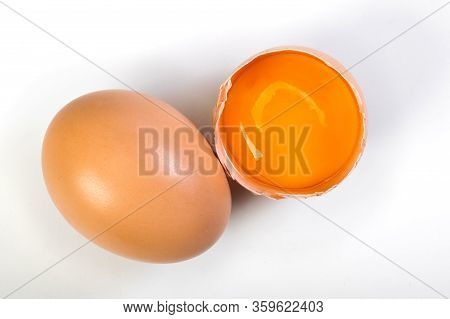 Cracked Egg With Egg Shell, Egg Yolk And Egg White On White Background. Top View.