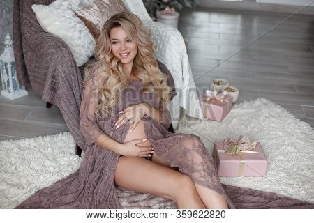 Pregnant Woman Feeling Happy While Taking Care Of Her Child. The Young Expecting Mother Holding Baby