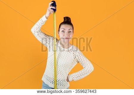 Surprised Smiling Girl Stands Next To A Stretched Measuring Tape And Measures Her Height, Isolated O