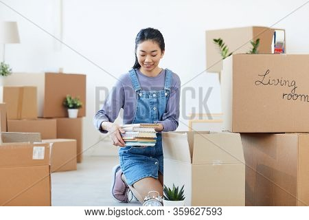 Full Length Portrait Of Young Asian Woman Packing Books To Cardboard Boxes And Smiling Happily Excit