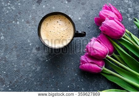 Cup Of Coffee With Foam And Bouquet Of Pink Tulips On Black Background. Breakfast On Mothers Day, Va