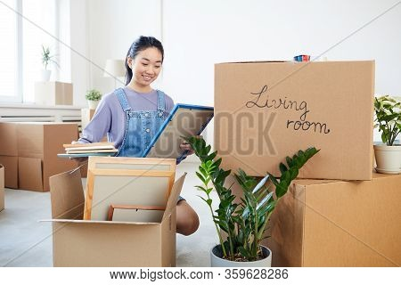 Full Length Portrait Of Young Asian Woman Packing Decor Items To Cardboard Boxes And Smiling Happily