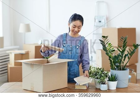 Waist Up Portrait Of Young Asian Woman Packing Or Unpacking Cardboard Box And Smiling Happily While