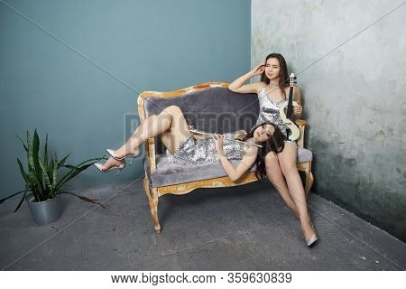 Two Girl The Musician With A Violin And A Flute In The Hands Of The Bright Stage Clothes. A Woman Pl