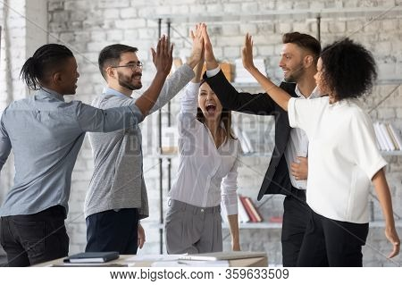 Excited Successful Multiracial Business People Giving High Five, Celebrating Win.