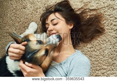 Portrait Young Joyful Woman Lying On Carpet With Cute Pet. Happy Girl Playing And Stroking Welsh Cor