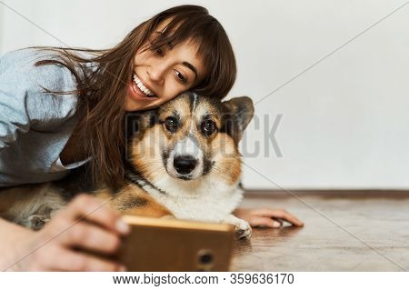 Portrait Laughting Young Woman Hugging Cute Welsh Corgi Dog Dog And Taking Selfie With Pet On Smartp