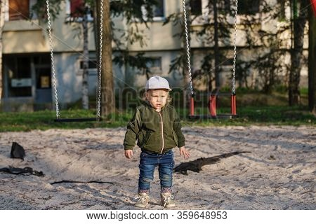 The Girl Stands Alone In The Playground, Which Is Closed By A Virus