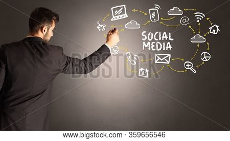 businessman drawing social media icons with SOCIAL MEDIA inscription, new media concept
