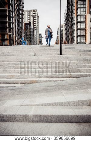 Man In A Raincoat Descending The Staircase