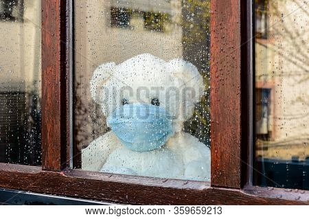 Sad Teddy Bear In Medical Mask On Quarantine For Covid-19 Looks Out Of The Window With Rain Drops. S