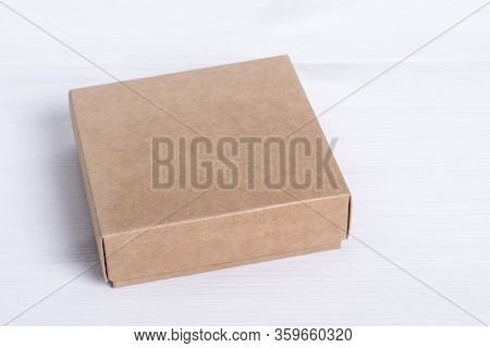 Blank Cardboard Box Package Isolated On White Wood Background. Craft Paper Box Side View. Small Squa