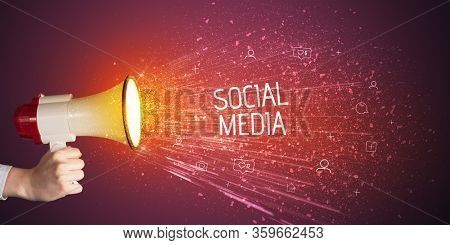 Young woman yelling to loudspeaker with SOCIAL MEDIA inscription, social networking concept