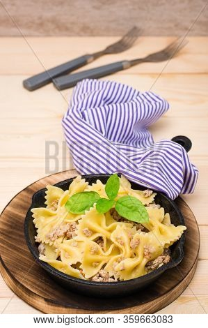 Ready-to-eat Pasta Navy With Minced Meat And Basil Leaves In A Iron Frying Pan On A Wooden Table. Ru