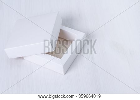 Open Empty White Gift Box With A Lid On Isolated Wooden Background. Side View, Square Box. Elegant E