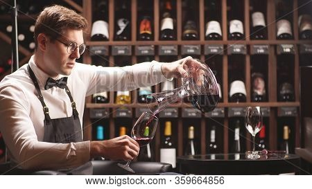 Young Sommelier Pours Wine From A Decanter Into A Wine Glass. Wine Tasting Process Close-up.