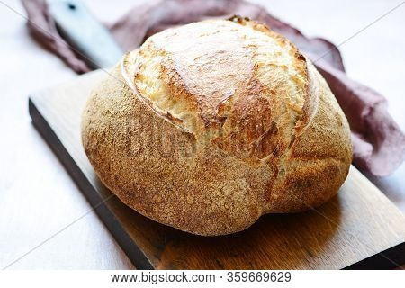 Homemade Freshly Baked Country Bread  Made From Wheat And Whole Grain Flour On A Gray-blue Backgroun