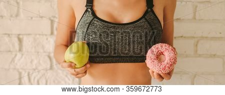 Closeup Young Sports Woman Hold Apple And Donut In Hands. Sexy Slim Fitness Girl Decide To Choose Be