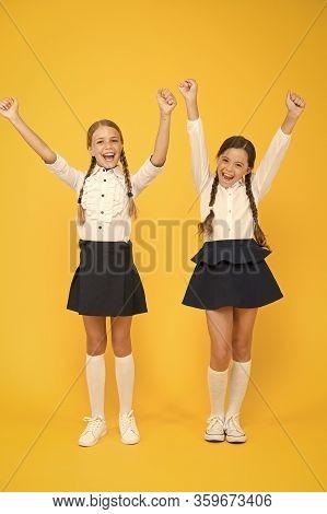 Enjoying Success. Happy Children Celebrating Success On Yellow Background. Little Schoolgirls Being