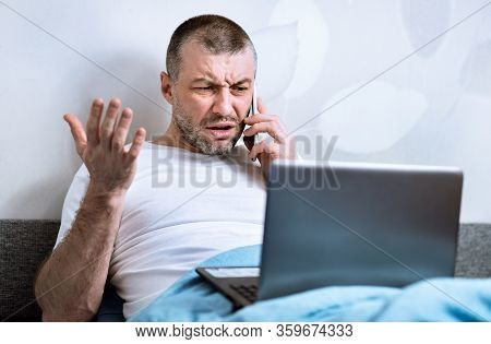Discontented Customer. Displeased Man Talking On Phone Sitting With Laptop In Bed At Home.