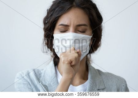 Young Unhealthy Woman In Facial Medical Facemask Coughing.