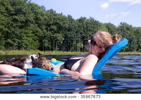 Pretty Young Woman And Sheltland Sheepdog Sleeping Together On A Floating Chair On A Lake