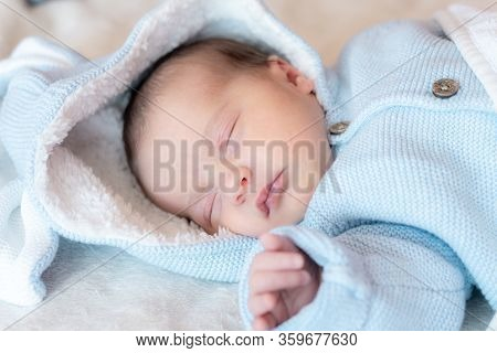 Newborn Baby Close-up. Side View Of A Newborn Baby Sleeping Soundly On His Back In A Blue Blouse Wit