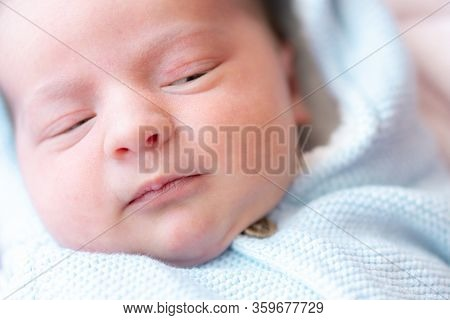 Close Up Portrait Of A Newborn Baby. Close-up Face Of Newborn Baby With Open Eyes. A Newborn Is Look
