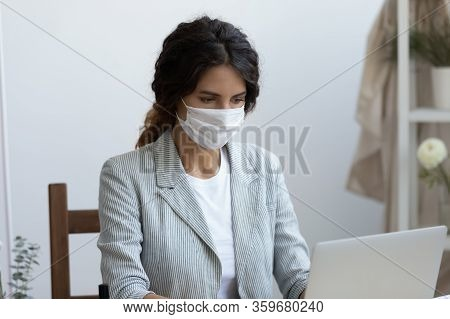 Businesswoman In Virus Protective Facemask Working On Computer In Office.
