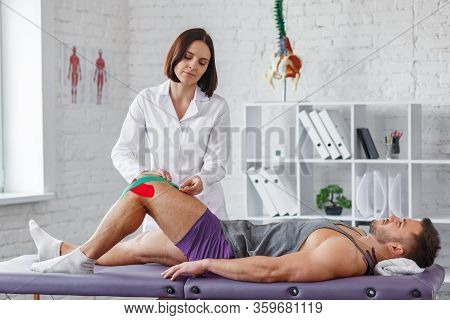 Kinesiology Taping.physical Therapist Applying Kinesiology Tape To Patient Knee.therapist Treating I