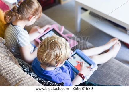 Children Using Their Tablet Device To Play Computer Games And Use Educational Apps