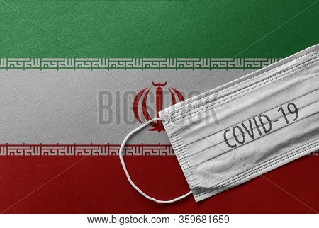 An Individual Face Medical Surgical Mask On Iran National Flag Background. Health Mask. Protection A