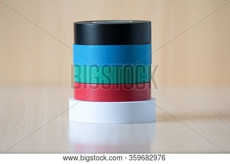 Four Colorful Insulating Tapes To Insulate The Twist Of Electrical Wires. Insulating Tapes On A Wood