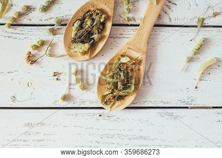 Natural Organic Herbal Green Tea In Wooden Spoons On White Vintage Background.
